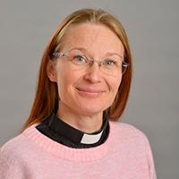 Nainen, jolla vaaleanpunainen pusero ja musta papin paita